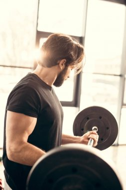 side view of handsome sportsman training with barbell in gym