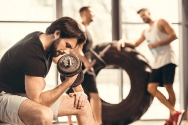 side view of muscular young man lifting dumbbell in gym