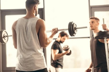 young sportsmen training with barbells in sports center