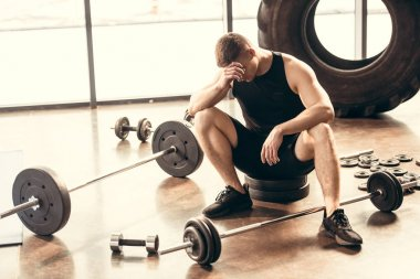 upset young sportsman sitting with dumbbells and barbells in gym