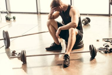 high angle view of upset young sportsman sitting with dumbbells and barbells in gym
