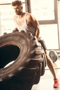 athletic young man in sportswear training with tire in gym