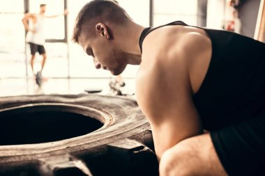 side view of muscular young sportsman exercising with tire in gym