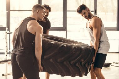 athletic young sportsmen lifting tyre together in gym