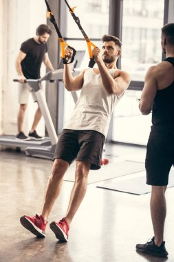 full length view of sporty young man training with resistance bands in gym