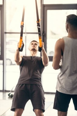 cropped shot of sporty man looking at muscular man training with suspension straps in gym