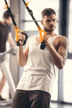 handsome muscular young man training with resistance bands and looking away in gym
