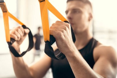 close-up view of muscular young man training with suspension straps in gym