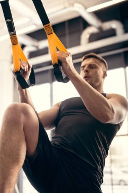 low angle view of young sportsman exercising with resistance bands in gym
