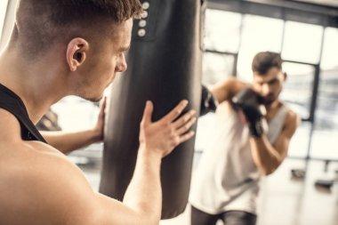 cropped shot of man holding punching bag while boxer hitting in gym