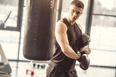 athletic young man in sportswear wearing boxing gloves and looking at punching bag in gym