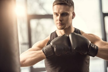 handsome muscular young sportsman in boxing gloves looking away while training in gym