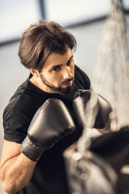 high angle view of handsome young man in boxing gloves training in gym