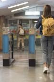 Fényképek női elegáns Traveler-a hátizsák halad át a beléptető kapu, és a férfi turisztikai mögött hátsó nézet