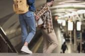 oříznutí záběru pár stylových turistů s batohy, drželi se za ruce, ve stanici metra