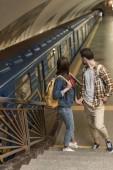 stylové cestovatele s batohy stojící na schodech u stanice metra