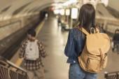 zadní pohled na hosty s batohy jít dolů na stanici metra