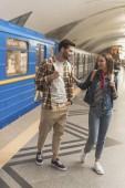 Fotografia elegante giovane coppia di turisti alla stazione della metropolitana