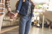 oříznutý obraz pár turistů, drželi se za ruce a stojí u stanice metra