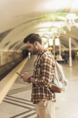 boční pohled na člověka s batohem a smartphone na stanici metra
