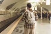 Fotografia vista posteriore delluomo alla moda con lo zaino alla stazione della metropolitana