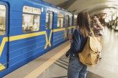 zadní pohled na stylové ženské turistovi batoh stojí u stanice metra