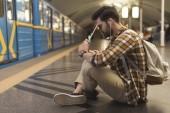 Fotografie junger Mann mit digital-Tablette und Ohrhörer sitzen auf Boden an u-Bahnstation