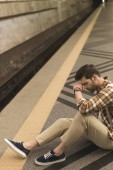 Photo latecomer frustrated man with backpack sitting on floor at subway station