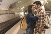 Fotografie boční pohled na ženské cestovatel všeobjímající přítel ve stanici metra