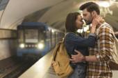 Fotografia vista laterale di elegante coppia di viaggiatori abbracciano alla stazione della metropolitana