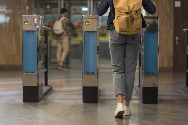 cropped shot of female stylish traveler with backpack passing through turnstiles and male tourist behind