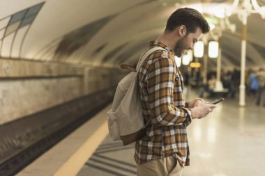 side view of smiling man with backpack typing on smartphone at subway station