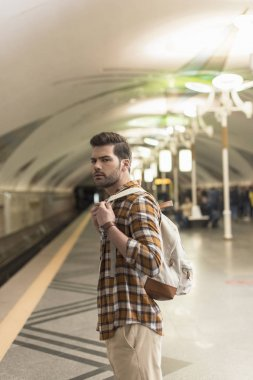 young man with backpack waiting train at metro station