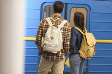 rear view of couple of stylish tourists with backpacks at subway station