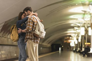 two stylish tourists embracing each other at subway station