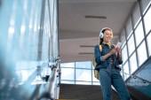 nízký úhel pohledu stylový ženské turista v sluneční brýle se sluchátky a smartphone na schodech v metru