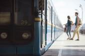 Fotografia colpo del primo piano del treno e coppia di turisti dietro alla stazione della metropolitana allaperto