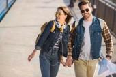 Fényképek pár elegáns turista napszemüveg a hátizsák, a fejhallgató és a Térkép, szabadtéri subway station