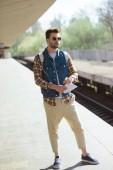 Fotografie Junge männliche Touristen in Sonnenbrille mit Karte in der hand warten Zug an Outdoor-u-Bahnstation