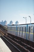 čelní pohled z vlaku ve stanici metra venkovní s budovami na pozadí