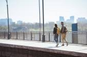 Fotografia vista in lontananza della coppia di turisti alla moda con zaini andando alla stazione della metropolitana allaperto