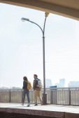 Photo rear view of couple of tourists going at outdoor subway station