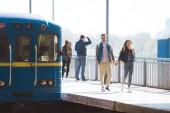 Fotografia elegante coppia di turisti che vanno alla stazione della metropolitana allaperto