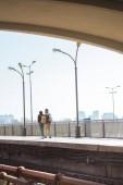 Fotografie vzdálený pohled stylové pár turistů na venkovní stanice