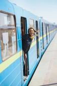 Fotografia donna alla moda sorridente in occhiali da sole guardando fuori dal treno alla stazione di metropolitana allaperto