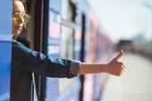 Fotografia donna alla moda in occhiali da sole in piedi in treno e facendo tonfo sul gesto alla stazione della metropolitana allaperto