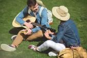 pár stylových turisté s batohy a kytara sedí na trávě a jíst sendviče