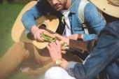 Oříznout záběr ženské cestovatel dát sendvič s přítelem akustická kytara