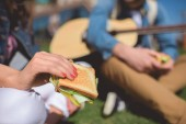 closeup shot of sandwich in female hand and man sitting with acoustic guitar