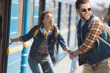 stylish female traveler calling boyfriend to going into train at outdoor subway station